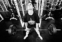 Female bodybuilder deadlifting 330 lbs barbell in gym