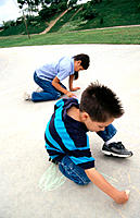 Children drawing on the sidewalk with chalk