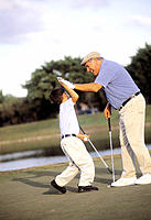 Mature man with grandson celebrating while playing golf