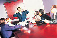 Executive plugging ears to request of others in meeting