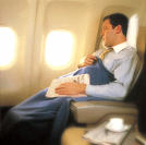 Businessman Sleeping on Airplane with Newspaper and Blanket