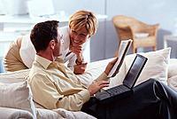 Paar sitzen Sofa Couch Laptop Notebook Zeitung unterhalten