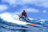 NorthShoreOahu woman standing rides small wave blue sky w/ clouds D1229