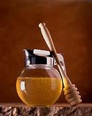 Honey in glass jug, honey spoon beside it