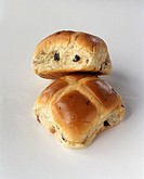 Two hot cross buns against white background