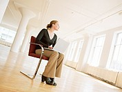 Businesswoman Sits in Empty Office Space, Laptop