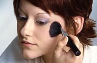 Young woman using makeup