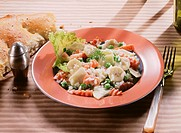 Rice salad with bananas, carrots and peas in deep plate
