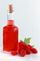 A bottle of raspberry vinegar, a few fresh raspberries