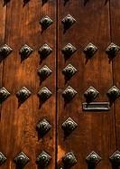 Wooden door with brass studs, close-up