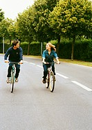 Man and woman riding bikes side by side, looking at each other, full length, front view