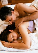 Couple lying in bed, man touching woman´s shoulder