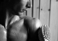 Bare-chested man, brush on arm, close-up, b&w