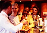 Group of business people raising glasses at bar