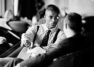 Businessmen sitting, discussing document, b&w
