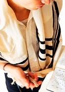 Jewish man praying with Torah, high angle view, close-up