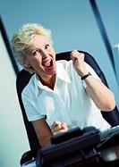 Businesswoman raising fist and smiling, portrait