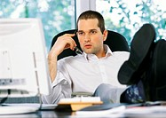 Businessman holding glasses next to face, looking at computer screen, sitting with feet on desk