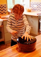 Child using salad spinner in kitchen, blurred motion