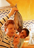 Two children in kitchen, one holding up a fish