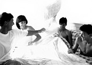 Family having pillow fight in bed, b&w