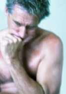 Topless mature man holding head with hand, close-up, portrait