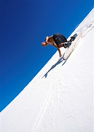 Man snowboarding down slope, low angle view