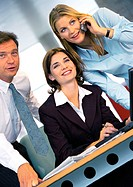 Three business people at desk, businesswoman using cell phone