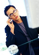 Businessman sitting at computer, using cell phone