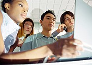 Four young people, one holding laptop, low angle view