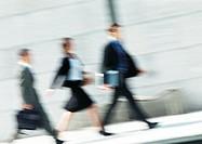 Business people walking in street, full length, tilt, blurred