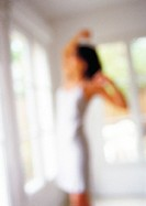 Woman stretching in front of window, blurred