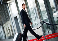 Businessman walking with luggage outside, side view