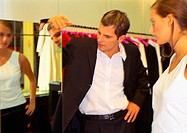 Woman looking into mirror inside clothing store, man looking at woman in mirror
