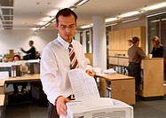 Businessman standing at printer in office