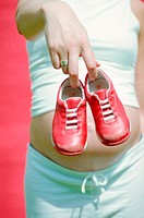 Mother-to-be holding child´s trainers