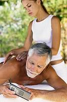 Man with cellphone being massaged