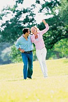 Man and woman striding through the park