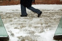 Person walking in snow past bus stop shelter