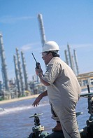 Worker with radio in hand at oil refinery
