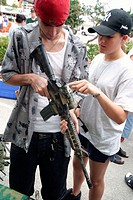 Couple looking at M-4 carbine confiscated in Afghanistan in display at the Air and Sea Show. Fort Lauderdale Beach. Florida. USA