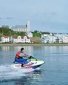 Man speeding on jet ski on sea, town of Akureyri in background