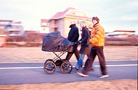 Three people walking along a footpath, one pushing a baby carriage