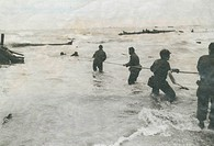 Soldiers pulling something from the ocean with a long rope