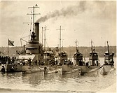 A battleship and five submaries in harbor
