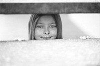 Young girl looking through fence