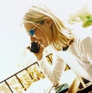 Blonde woman talking on cell phone, cafe patio, Italy