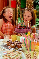 Two girls blowing out candles on birthday cake (1)
