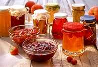 Various jams and jellies in jars and bowls