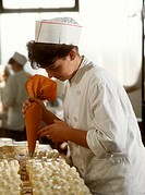 Female pastry chef decorating gateaux with piping bag